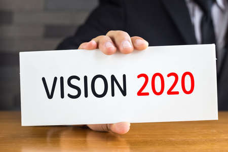 Vision 2020, message on white card and hold by  businessman Stock Photo