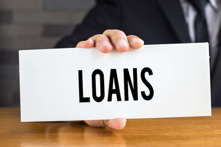 loans: Loans, message on white card and hold by  businessman
