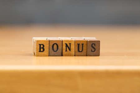 Bonus. word written on wood block Stock Photo