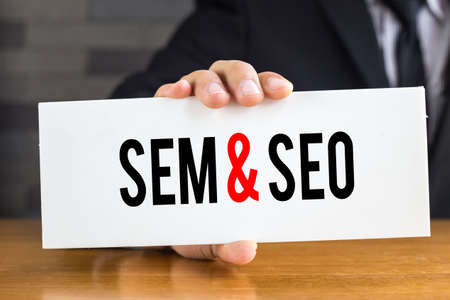 sem: SEM and SEO, message on white card and hold by businessman
