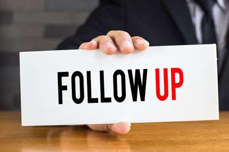 Follow-up, bericht op witte kaart en houd door zakenman
