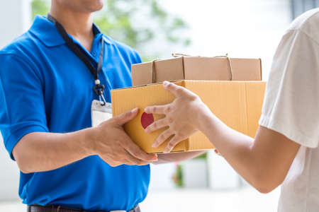 parcel service: Woman hand accepting a delivery of boxes from deliveryman