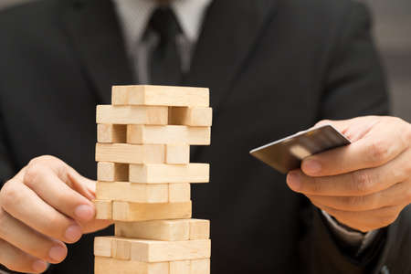 credit risk: Risk of credit card concept. Businessman choosing the wood block and holding credit card