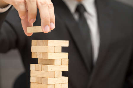 fragile economy: Businessman placing wooden block on a tower. Risk and strategy in business concept
