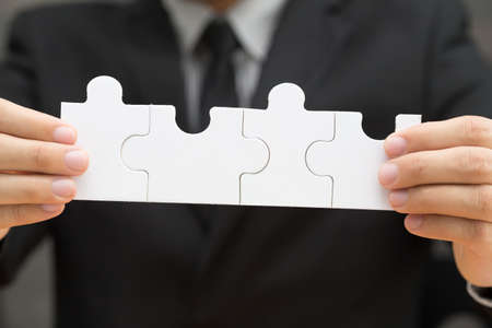 business puzzle: Businessman holding four jigsaw to connect