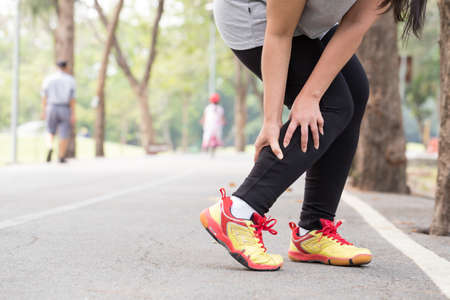 Sports injury. Cramp. Woman holding sore leg muscle while jogging