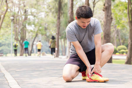 Sports injury. Man with pain in ankle while jogging