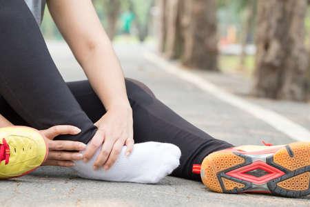 Blessures sportives. Femme avec douleur dans la cheville en faisant du jogging Banque d'images