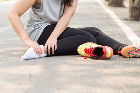sports injury: Sports injury. Woman with pain in ankle while jogging Stock Photo