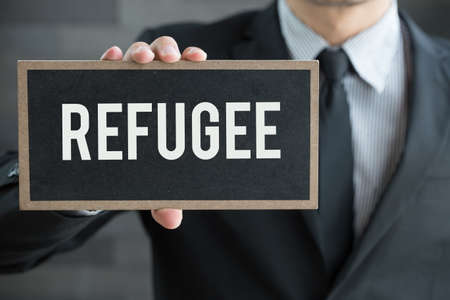 refugee: Refugee, message on blackboard and hold by businessman