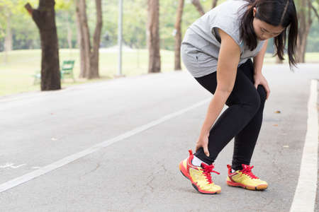 Sports injury. Woman with pain in ankle while jogging 免版税图像