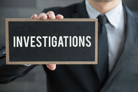 Investigations, message on blackboard and hold by businessman