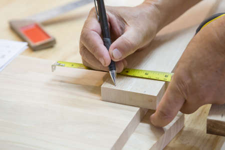 manual measuring instrument: Craftsman measuring wood with ruler Stock Photo