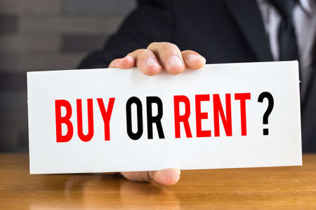 buying questions: Buy or rent, message on white card and hold by businessman
