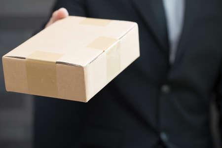 brown box: Businessman in suit giving brown box to someone