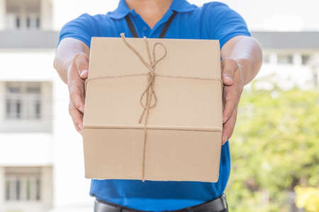 service: Delivery man holding a parcel box. Delivery service concept Stock Photo