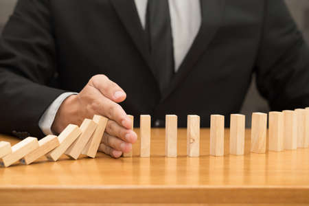 Hand of businessman stopping the domino effect. Risk control concept