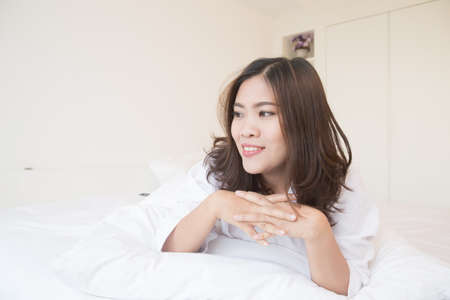 cookware: Young asian woman on the bed in the morning Stock Photo