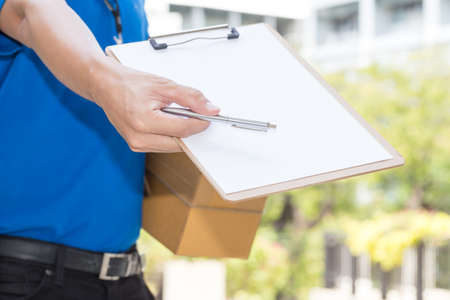 Delivery Man holding parcel and giving pen to client Stock Photo