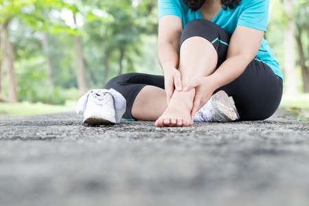 Sports injury. Woman with pain in ankle while jogging Standard-Bild