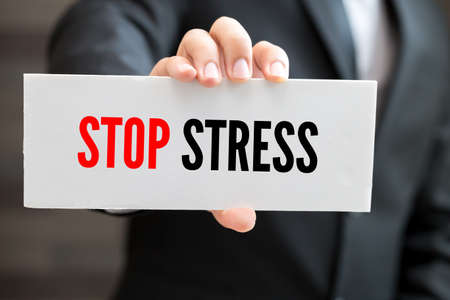 stressing: Stop stress, message on white card and hold by businessman