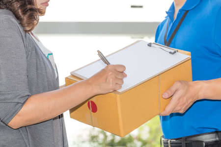Woman hand signing receipt of delivered package. Delivery concept. Receiving package Stock Photo
