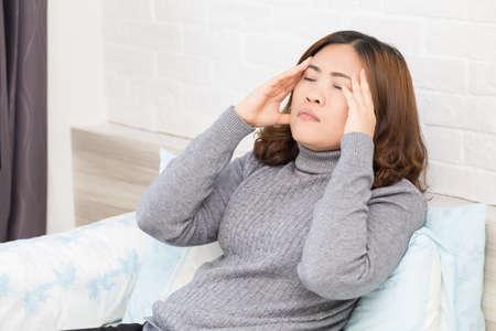 Asian woman with headache, migraine and dizziness