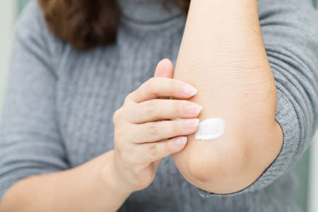 Woman takes care of elbow using cosmetic cream Stock Photo
