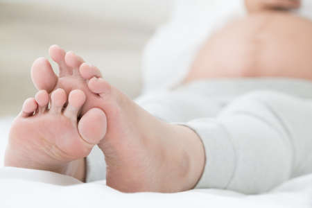 Southeast asian pregnant women with swelling feet, pain foot and lying on bed in the room. Swollen feet and fetal poisoning or toxicity concept