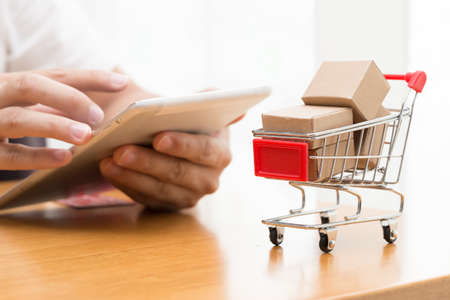 Hand man using the tablet and buy goods from a seller over the internet. online shopping concept