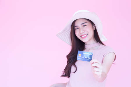 Beautiful young Asian woman smiling and presenting credit card with copy space pink background, Making payment for shopping online or flight ticket, Ecommerce concept