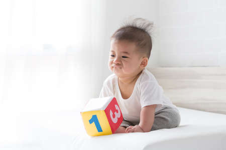 Asian baby boy be bored with toys Banque d'images - 115734650