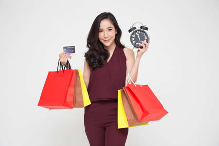 Midnight sale, Portrait of a happy young women in red dress holding shopping bags and black alarm clock, Year end sale or mid year sale promotion clearance for Shopaholic concept, Asian female model Stock Photo