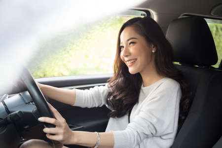 Asian women driving a car and smile happily with glad positive expression during the drive to travel journey, People enjoy laughing transport and relaxed happy woman on roadtrip vacation concept