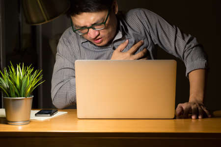 Symptoms of heart disease during overtime at night in the office, Working late and healthy concept Stockfoto