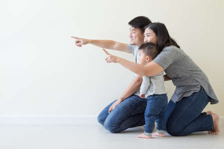 Happy asian family looking away and pointing up Foto de archivo