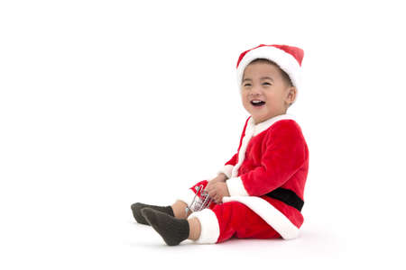 Happy asian baby boy laughing and having fun in a Christmas costume Santa Claus isolated on white background Stock Photo
