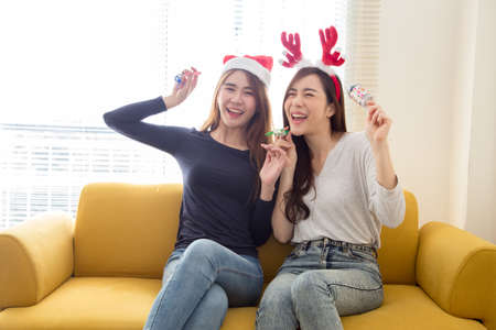 Happy friends two young asian woman laughing and having fun together with celebrating christmas or new year or birthday party on yellow sofa in the living room at home, Crazy day with friend concept