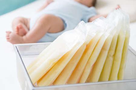 Leche materna congelada en bolsa de almacenamiento y bebé acostado sobre fondo