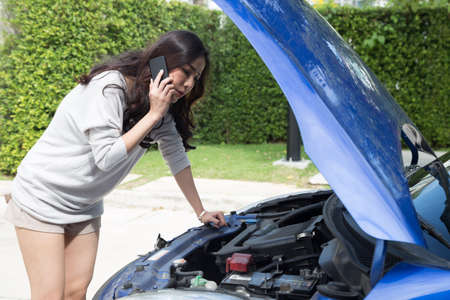 Young asian woman using mobile phone call a car mechanic while looking at broken down car on street, Calling for assistance breakdown or fixing concept Reklamní fotografie