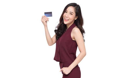 Ritratto di una giovane donna felice in abito rosso che tiene bancomat o carta di debito o di credito e utilizza per lo shopping online spendendo un sacco di soldi isolato su sfondo bianco, modello femminile asiatico