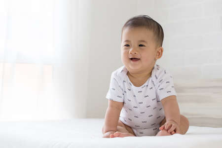 Baby boy smiling on white bed in the bedroom