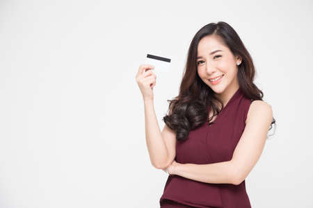 Young beautiful Asian woman smiling, showing, presenting credit card for making payment or paying online business, Pay a merchant or as a cash advance for goods, Cardholder or A person who owns a card Banque d'images - 115739879