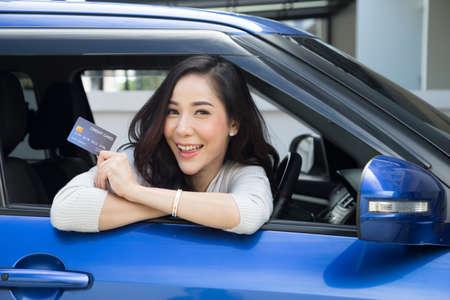 Feliz hermosa mujer asiática sentada dentro de un coche nuevo azul y mostrando el pago de aceite con tarjeta de crédito, pago de una llanta, mantenimiento en el garaje, pago por reabastecimiento de combustible en la gasolinera, financiación automotriz
