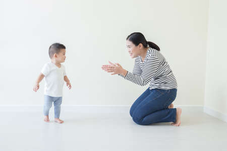 Asian baby boy learning to walk with watching and take care by mom, Son take first steps at home