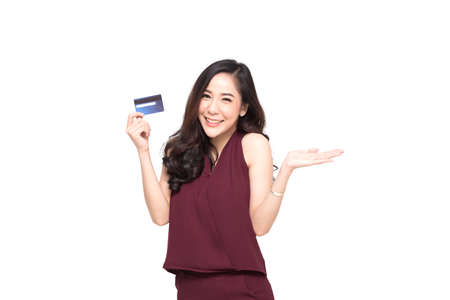 Young smiling beautiful Asian woman presenting credit card in hand for making payment shopping isolated on white background Standard-Bild