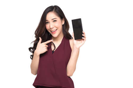 Portrait of a cheerful beautiful girl wearing red dress and showing or presenting mobile phone application and pointing finger to smartphone on hand isolated over white background, Asian Thai model Stockfoto