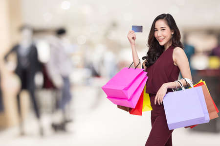 Portrait of a happy women in red dress holding shopping bags and credit card with blurred mall background, Year end sale or mid year sale promotion clearance for Shopaholic concept, Asian model