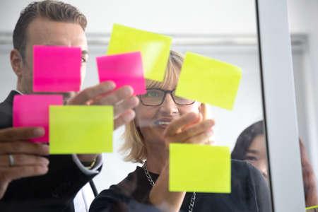 IT-medewerker die zijn taken volgt op het kanbanbord. Taakcontrole gebruiken van agile ontwikkelingsmethodologie. Teamleden die een plakbriefje aan het scrum-taakbord op kantoor bevestigen