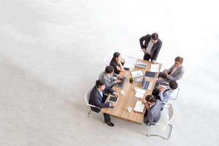 Draufsicht auf eine Gruppe multiethnischer beschäftigter Menschen, die in einem Büro arbeiten, Luftbild mit Geschäftsmann und Geschäftsfrau, die um einen Konferenztisch mit leerem Kopienraum sitzen, Geschäftstreffenkonzept